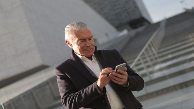 外出中にスマホで仕事のメールを確認しているビジネスパーソン