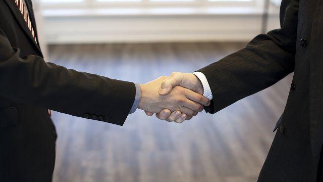 がっちり握手をする欧米人とのビジネスの様子