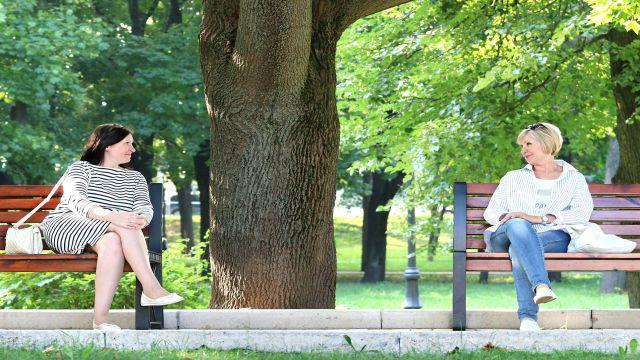 「私もそう思う!」と公園のベンチに座って会話している二人の女性