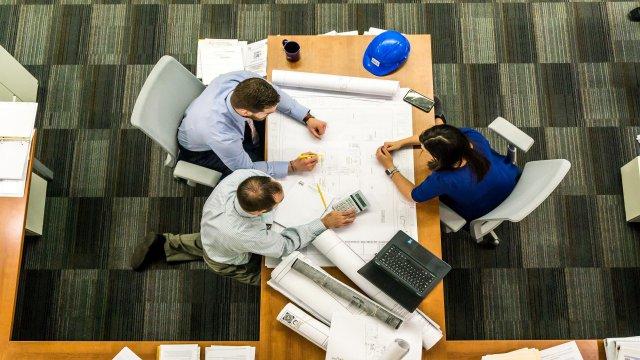 仕事のミーティングで意見交換をしている3人の同僚