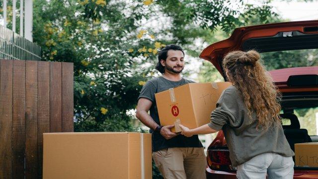 「問題ないよ」と言いながら友人の車から荷物を出すのを手伝っている男性