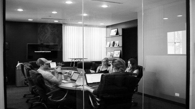 打ち合わせ室で今後のビジネス戦略を練っている4人の同僚